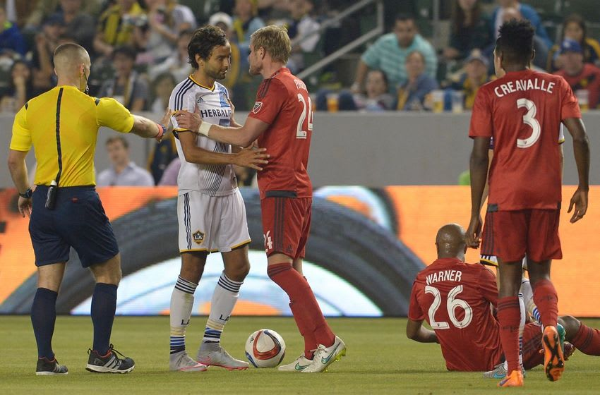 Jul 4, 2015; Carson, CA, USA; Referee Chris Penso issues a yellow card to Los Angeles Galaxy midfielder Baggio Husidic (6) as Toronto FC defender Damien Perquis (24) pushes him from giving a hand to midfielder Collen Warner (26) in the second half of the game at StubHub Center. Galaxy won 4-0. Mandatory Credit: Jayne Kamin-Oncea-USA TODAY Sports