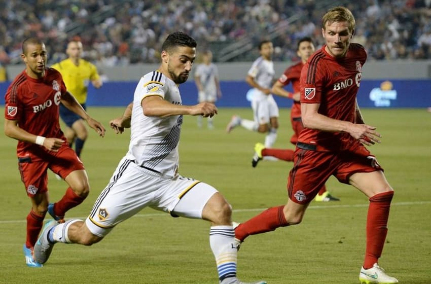 Jul 4, 2015; Carson, CA, USA; Los Angeles Galaxy midfielder Sebastian Lletget (17) heads to the goal as Toronto FC defender Damien Perquis (24) defends in the second half of the game at StubHub Center. Galaxy won 4-0. Mandatory Credit: Jayne Kamin-Oncea-USA TODAY Sports