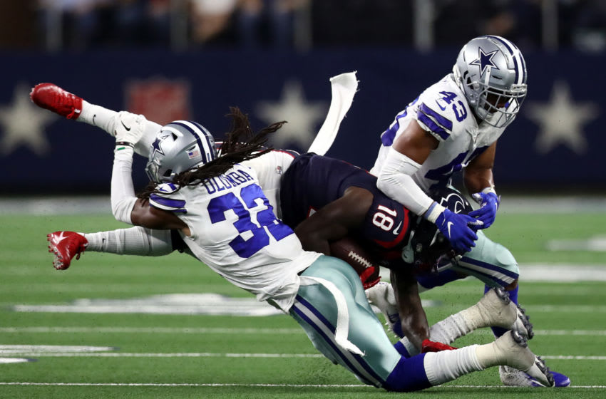 ARLINGTON, TEXAS - AUGUST 24: Johnnie Dixon #18 of the Houston Texans is tackled by Donovan Olumba #32 and Nate Hall #43 of the Dallas Cowboys during a NFL preseason game at AT&T Stadium on August 24, 2019 in Arlington, Texas. (Photo by Ronald Martinez/Getty Images)