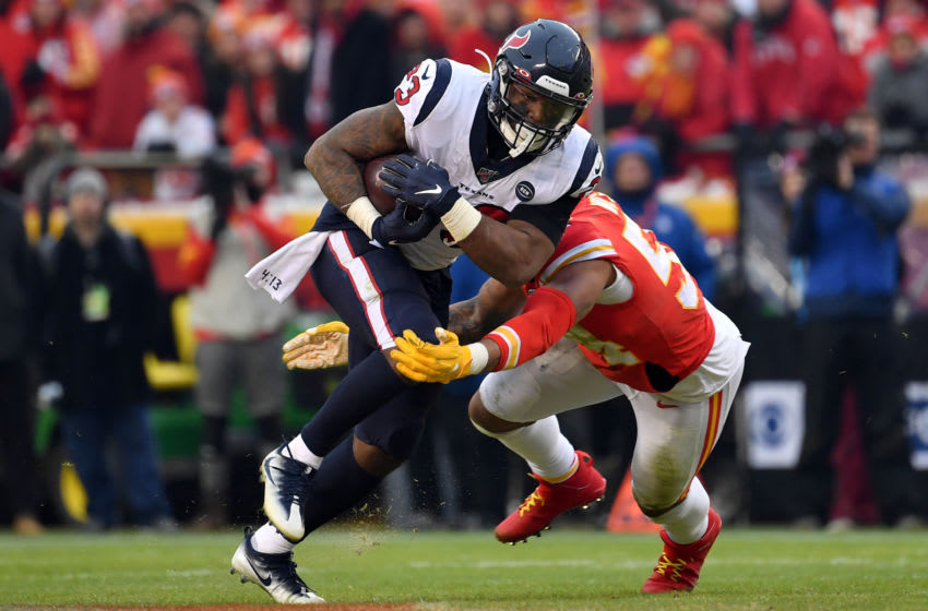 KANSAS CITY, MISSOURI - JANUARY 12: Carlos Hyde #23 of the Houston Texans is tackled by the defense of the Kansas City Chiefs during the AFC Divisional playoff game at Arrowhead Stadium on January 12, 2020 in Kansas City, Missouri. (Photo by Peter Aiken/Getty Images)