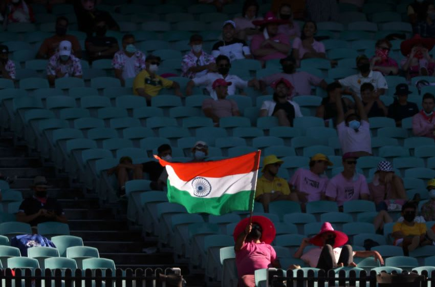 A fan holds an Indian national flag as he watches the game on the third day of the third cricket Test match between Australia and India at the Sydney Cricket Ground (SCG) in Sydney on January 9, 2021. (Photo by DAVID GRAY / AFP) / -- IMAGE RESTRICTED TO EDITORIAL USE - STRICTLY NO COMMERCIAL USE -- (Photo by DAVID GRAY/AFP via Getty Images)