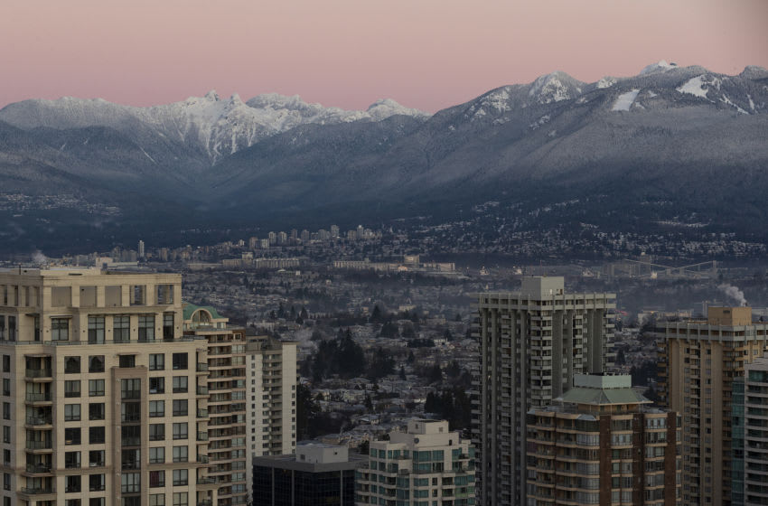 BURNABY, BRITISH COLUMBIA - DECEMBER 22: A view of metro Vancouver skyline at sunrise against the two pointed peaks aka