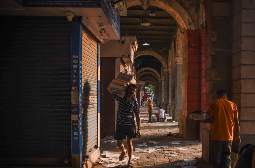 MUMBAI, INDIA - APRIL 29: A man carries a stack of newspapers down a near-deserted alley during a lockdown imposed to try and contain the spread of Covid-19 on April 29, 2021 in Mumbai, India. With recorded cases crossing 380,000 a day and 3000 deaths in the last 24 hours, India has more than 2 million active cases of Covid-19, the second-highest number in the world after the U.S. A new wave of the pandemic has totally overwhelmed the country's healthcare services and has caused crematoriums to operate day and night as the number of victims continues to spiral out of control. (Photo by Fariha Farooqui/Getty Images)