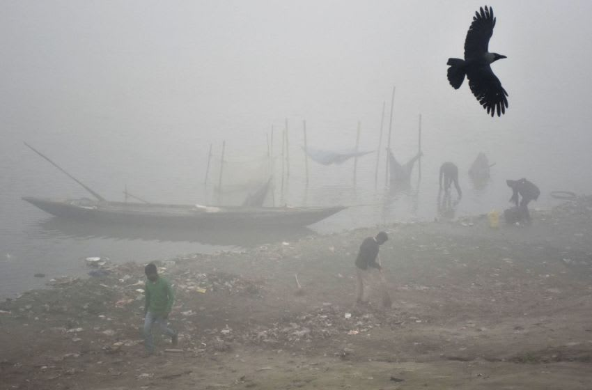 Indian labourers work on the banks of the Brahmaputra River after fisherman arrived with their catch on a foggy morning in Guwahati on January 5, 2018. / AFP PHOTO / Biju BORO (Photo credit should read BIJU BORO/AFP via Getty Images)