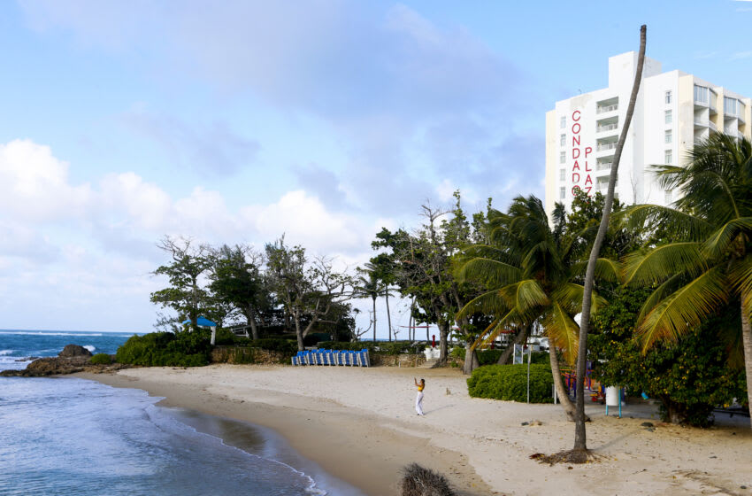SAN JUAN, PUERTO RICO - MARCH 22: A lone tourist takes a selfie at the Condado Hotel beach, disregarding an island-wide curfew imposed by Governor Wanda Vázquez eight days ago closing all nonessential businesses to contain the spread of the coronavirus on March 22, 2020 in San Juan, Puerto Rico. On a normal Sunday afternoon this spot would be full of locals and tourists. (Photo by Jose Jimenez/Getty Images)