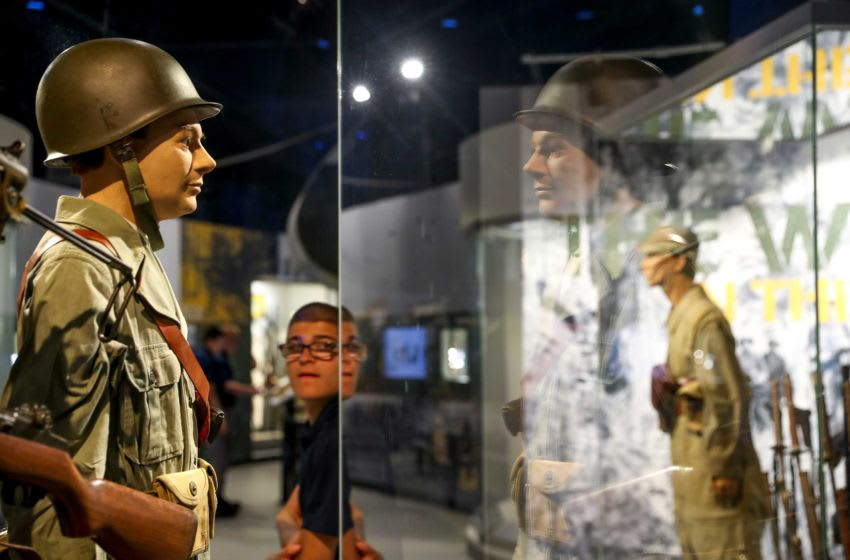 Visitors walk by displays of what an actual 101st Airborne Division soldier would have worn on D-Day at the Pratt Museum in Fort Campbell, KY., on Tuesday, June 4, 2019. Hpt D Day History 75th Anniversary 13