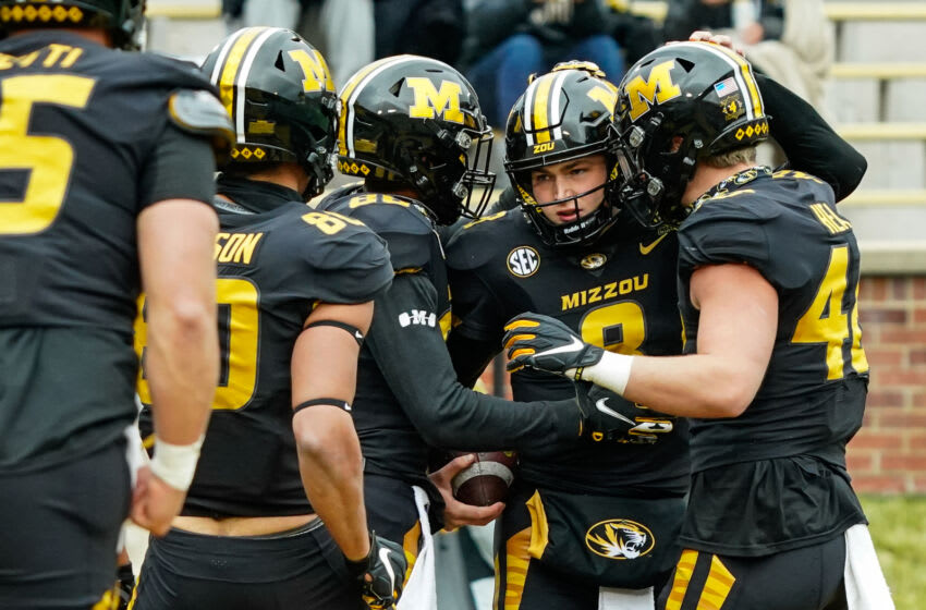 Dec 12, 2020; Columbia, Missouri, USA; Missouri Tigers quarterback Connor Bazelak (8) is congratulated by teammates after scoring a touchdown against the Georgia Bulldogs during the first half at Faurot Field at Memorial Stadium. Mandatory Credit: Jay Biggerstaff-USA TODAY Sports