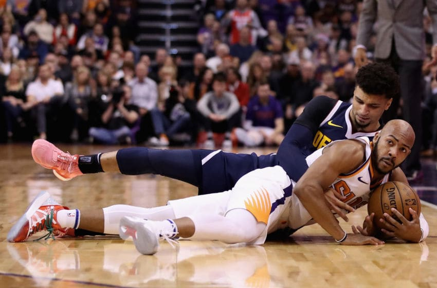 PHOENIX, ARIZONA - DECEMBER 23: Jevon Carter #4 of the Phoenix Suns grabs a loose ball ahead of Jamal Murray #27 of the Denver Nuggets during the first half of the NBA game at Talking Stick Resort Arena on December 23, 2019 in Phoenix, Arizona. The Nuggets defeated the Suns 113-111. (Photo by Christian Petersen/Getty Images)