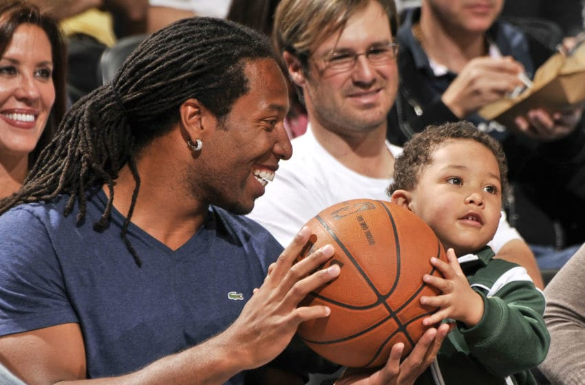 ORLANDO, FL - MARCH 9: Larry Fitzgerald of the Phoenix Cardinals smiles holding the game ball with his son Devin as he sits courtside during the game between the Los Angeles Clippers and the Orlando Magic on March 9, 2010 at Amway Arena in Orlando, Florida. NOTE TO USER: User expressly acknowledges and agrees that, by downloading and or using this photograph, User is consenting to the terms and conditions of the Getty Images License Agreement. Mandatory Copyright Notice: Copyright 2010 NBAE (Photo by Fernando Medina/NBAE via Getty Images)