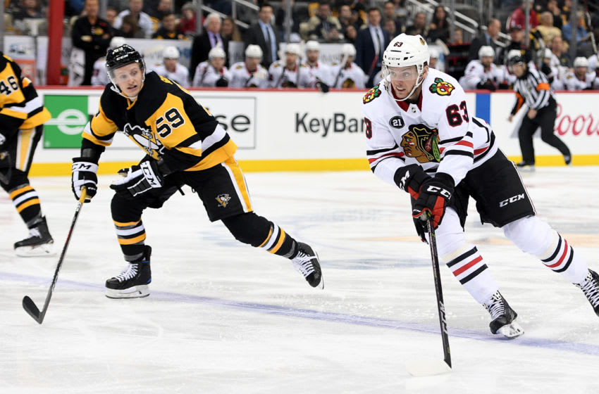 Carl Dahlstrom #63 of the Chicago Blackhawks skates with the puck against Jake Guentzel #59 of the Pittsburgh Penguins. (Photo by Justin Berl/Getty Images)
