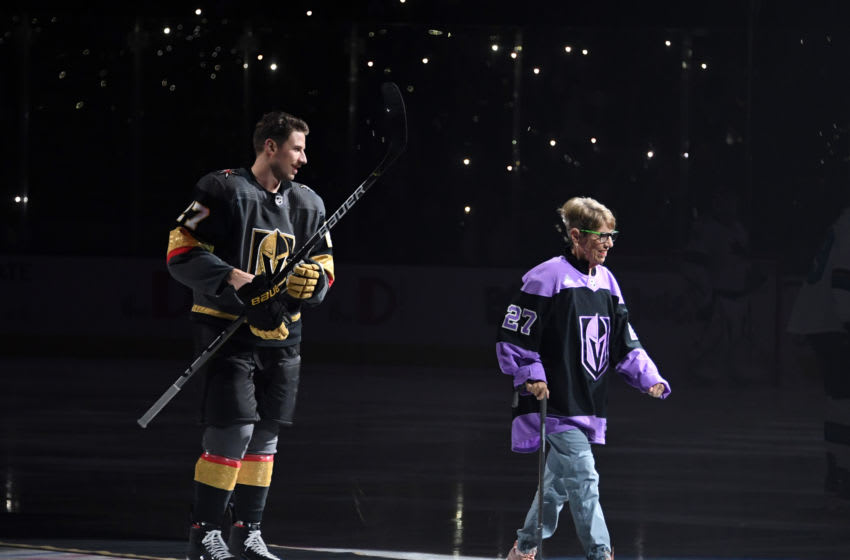 Shea Theodore #27 of the Vegas Golden Knights escorts his grandmother Kay Darlington off the ice after performing the ceremonial puck drop. (Photo by Ethan Miller/Getty Images)