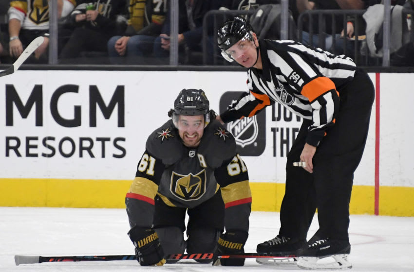 LAS VEGAS, NEVADA - DECEMBER 28: Referee Dean Morton checks on Mark Stone #61 of the Vegas Golden Knights after he was hurt in the third period of a game against the Arizona Coyotes at T-Mobile Arena on December 28, 2019 in Las Vegas, Nevada. The Golden Knights defeated the Coyotes 4-1. (Photo by Ethan Miller/Getty Images)