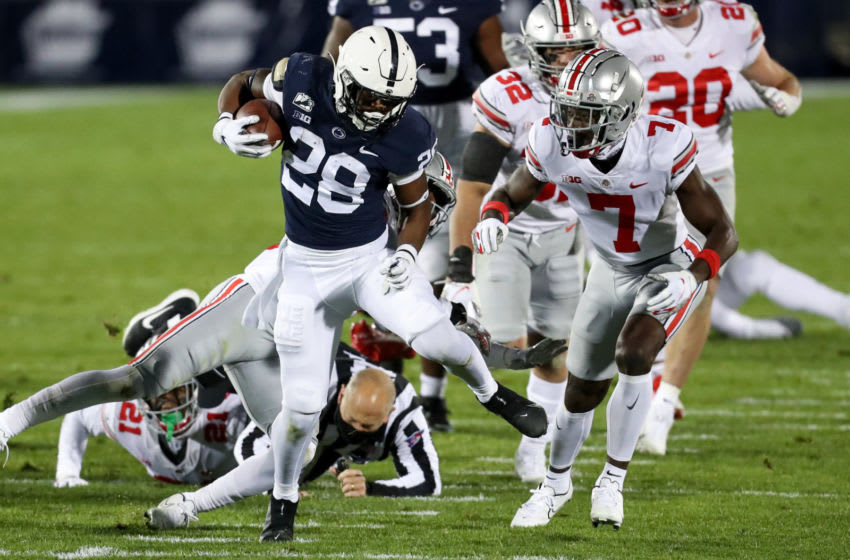 Oct 31, 2020; University Park, Pennsylvania, USA; Penn State Nittany Lions running back Devyn Ford (28) runs with the ball during the first quarter against the Ohio State Buckeyes as an official falls down at Beaver Stadium. Mandatory Credit: Matthew OHaren-USA TODAY Sports