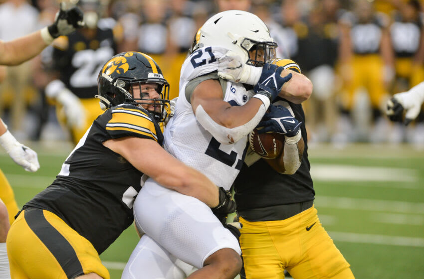 Iowa Hawkeyes offensive lineman Asher Fahey (left) and defensive back Jack Koerner (right) tackle Penn State Nittany Lions running back Noah Cain (21) during the third quarter at Kinnick Stadium. Mandatory Credit: Jeffrey Becker-USA TODAY Sports