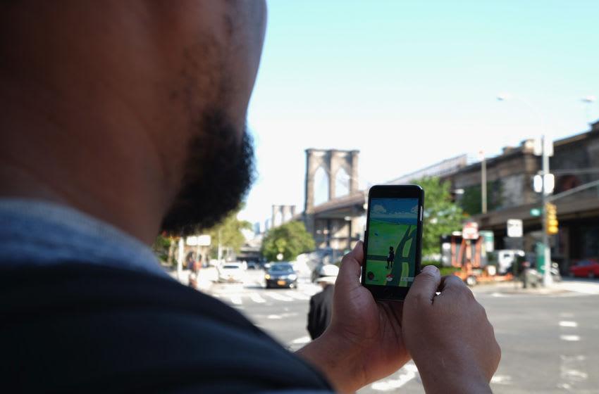 NEW YORK, NY - AUGUST 04: A man catches Pokemon near the Brooklyn Bridge as the Pokemon Go Craze Hits New York City on August, 4 2016 in New York City. (Photo by Michael Loccisano/Getty Images)