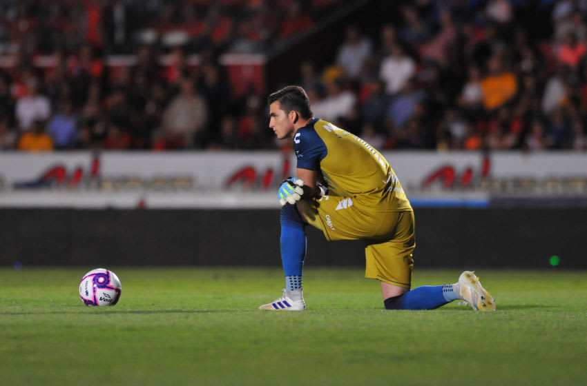 Tiburones goalkeeper Sebastian Jurado kneels behind the ball as part of his team's protest against the Veracruz owner. (Photo by VICTOR CRUZ/AFP via Getty Images)