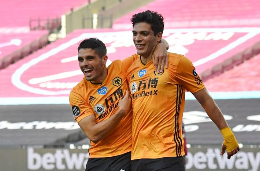Wolverhampton Wanderers' Mexican striker Raul Jimenez (R) celebrates scoring the opening goal with Wolverhampton Wanderers' Portuguese midfielder Pedro Neto (L) during the English Premier League football match between West Ham United and Wolverhampton Wanderers at The London Stadium, in east London on June 20, 2020. (Photo by Ben STANSALL / POOL / AFP) / RESTRICTED TO EDITORIAL USE. No use with unauthorized audio, video, data, fixture lists, club/league logos or 'live' services. Online in-match use limited to 120 images. An additional 40 images may be used in extra time. No video emulation. Social media in-match use limited to 120 images. An additional 40 images may be used in extra time. No use in betting publications, games or single club/league/player publications. / (Photo by BEN STANSALL/POOL/AFP via Getty Images)