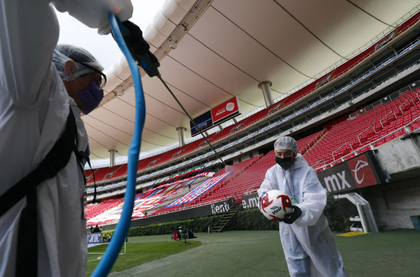 ZAPOPAN, MEXICO - JULY 12: Staff members of the Akron Stadium sanitize the balls before the match between Atlas and Tigres UANL as part of the friendship tournament Copa GNP por Mexico at Akron Stadium on July 12, 2020 in Zapopan, Mexico. (Photo by Refugio Ruiz/Getty Images)