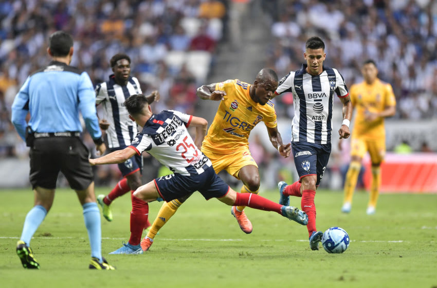 MONTERREY, MEXICO - SEPTEMBER 28: Jonathan González, #25 of Monterrey, fights for the ball with Enner Valencia, #13 of Tigres, while observed by referee César Ramos during the 12th round match between Monterrey and Tigres UANL as part of the Torneo Apertura 2019 Liga MX at BBVA Stadium on September 28, 2019 in Monterrey, Mexico. (Photo by Azael Rodriguez/Getty Images)