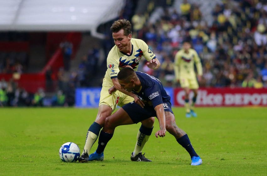 MEXICO CITY, MEXICO - SEPTEMBER 14: Fernando Gonzalez (L) of America fights for the ball with Bryan Mendoza (R) of Pumas during the 9th round match between America and Pumas UNAM as part of the Torneo Apertura 2019 Liga MX at Azteca Stadium on September 14, 2019 in Mexico City, Mexico. (Photo by Mauricio Salas/Jam Media/Getty Images)
