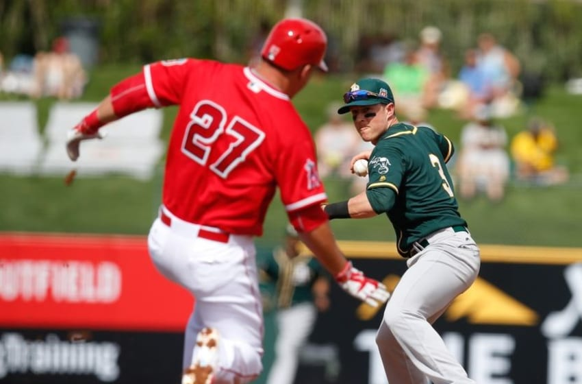 Mar 3, 2016; Tempe, AZ, USA; Oakland Athletics left fielder Chris Coghlan (3) turns the double play while avoiding Los Angeles Angels center fielder Mike Trout (27) in the second inning during a spring training game at Tempe Diablo Stadium. Mandatory Credit: Rick Scuteri-USA TODAY Sports
