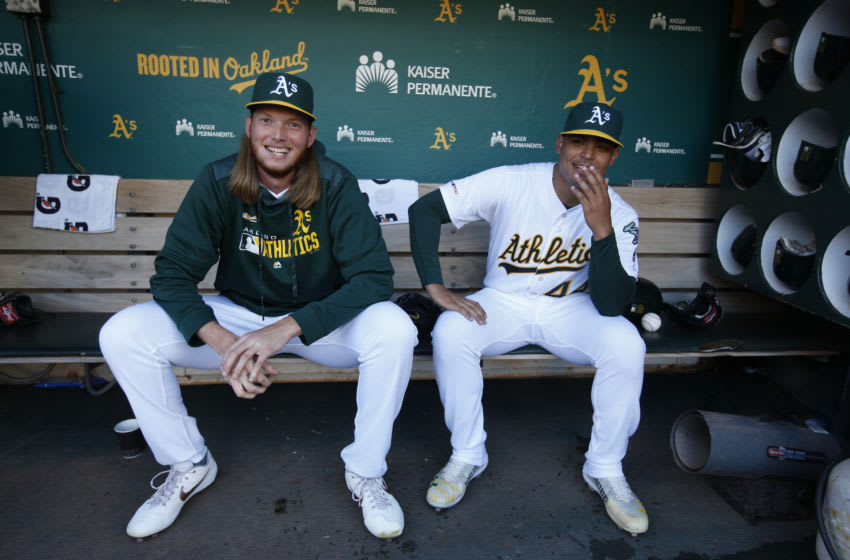 OAKLAND, CA - SEPTEMBER 21: A.J. Puk #31 and Jesus Luzardo #44 of the Oakland Athletics sit in the dugout prior to the game against the Texas Rangers at the Oakland-Alameda County Coliseum on September 21, 2019 in Oakland, California. The Athletics defeated the Rangers 12-3. (Photo by Michael Zagaris/Oakland Athletics/Getty Images)