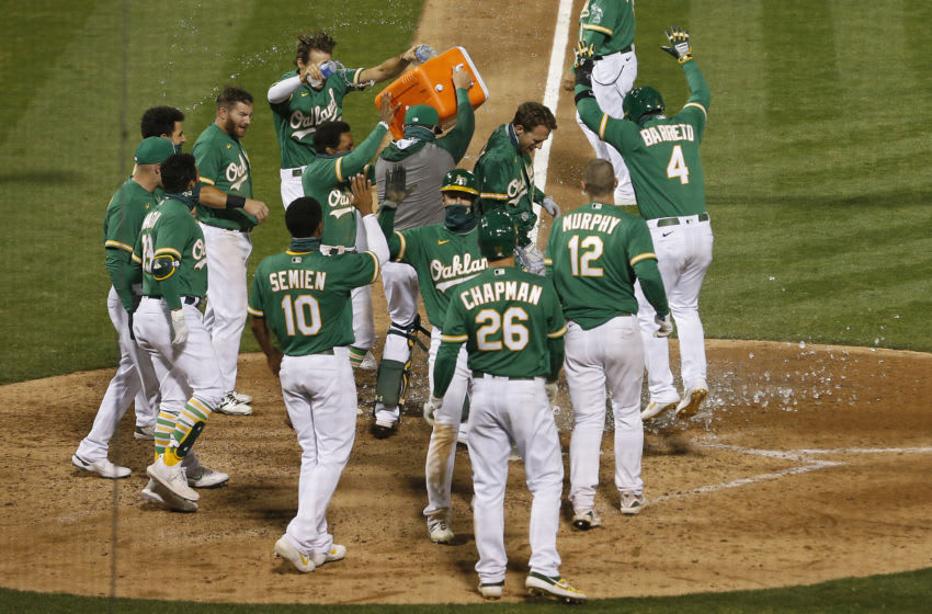 OAKLAND, CALIFORNIA - AUGUST 04: Stephen Piscotty #25 of the Oakland Athletics celebrates with his teammates at home plate after hitting a walk-off grand slam to win the game against the Texas Rangers at Oakland-Alameda County Coliseum on August 04, 2020 in Oakland, California. (Photo by Lachlan Cunningham/Getty Images)