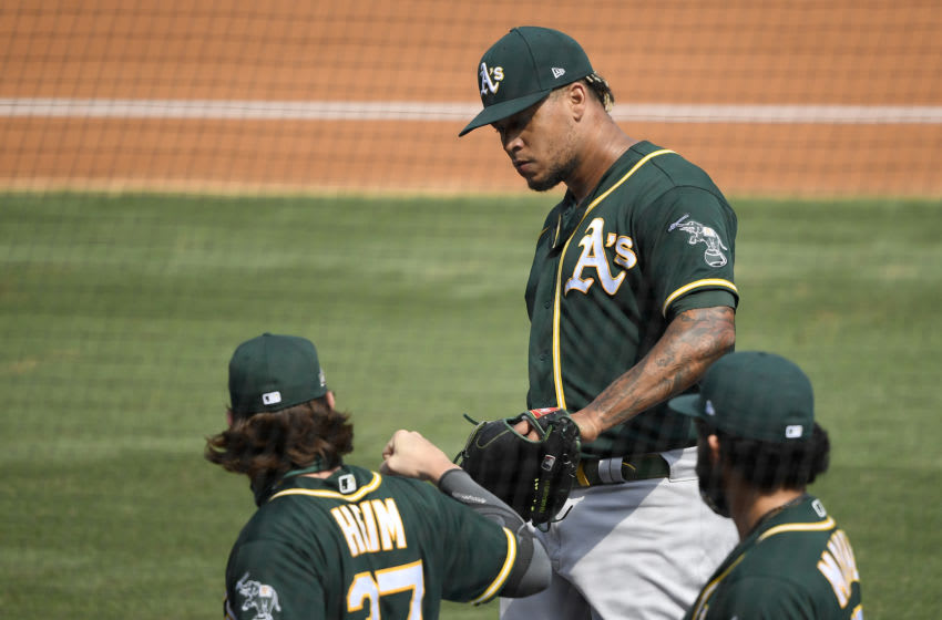 LOS ANGELES, CALIFORNIA - OCTOBER 08: Frankie Montas #47 of the Oakland Athletics is congratulated by teammates Jonah Heim #37 and Sean Manaea #55 after the third inning against the Houston Astros in Game Four of the American League Division Series at Dodger Stadium on October 08, 2020 in Los Angeles, California. (Photo by Kevork Djansezian/Getty Images)