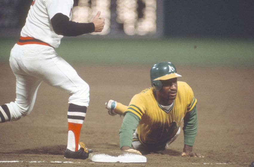 BOSTON, MA - CIRCA 1975: Claudell Washington #19 of the Oakland Athletics dives back into first base against the Boston Red Sox during an Major League Baseball game circa 1975 at Fenway Park in Boston, Massachusetts. Washington played for the Athletics from 1974-76. (Photo by Focus on Sport/Getty Images)