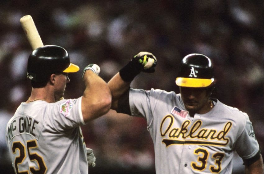 CINCINNATI, OH - OCTOBER 17, 1990: Jose Canseco #33 of the Oakland Athletics is congratulated by Mark McGwire #25 of the Oakland Athletics (The Bash Brothers) after hitting a home run against the Cincinnati Reds in Game 2 of the 1990 World Series on October 17,1990 in Cincinnati, Ohio. (Photo by Ronald C. Modra/Getty Images)
