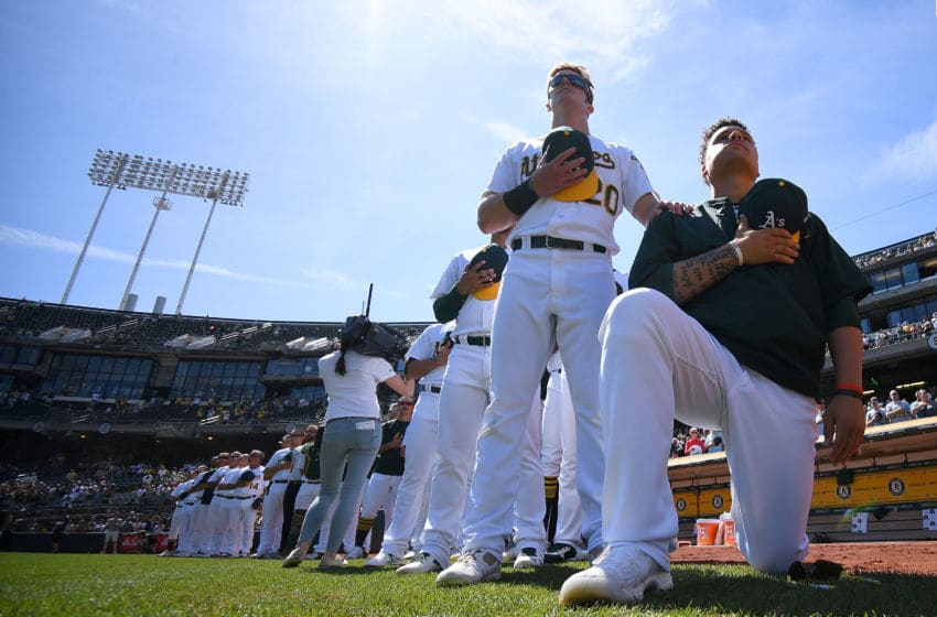 OAKLAND, CA - SEPTEMBER 24: Bruce Maxwell #13 of the Oakland Athletics kneels in protest next to teammate Mark Canha #20 duing the singing of the National Anthem prior to the start of the game against the Texas Rangers at Oakland Alameda Coliseum on September 24, 2017 in Oakland, California. (Photo by Thearon W. Henderson/Getty Images)