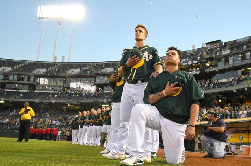 OAKLAND, CA - SEPTEMBER 26: Bruce Maxwell #13 of the Oakland Athletics kneels in protest next to teammate Mark Canha #20 duing the singing of the National Anthem prior to the start of the game against the Seattle Mariners at Oakland Alameda Coliseum on September 26, 2017 in Oakland, California. (Photo by Thearon W. Henderson/Getty Images)