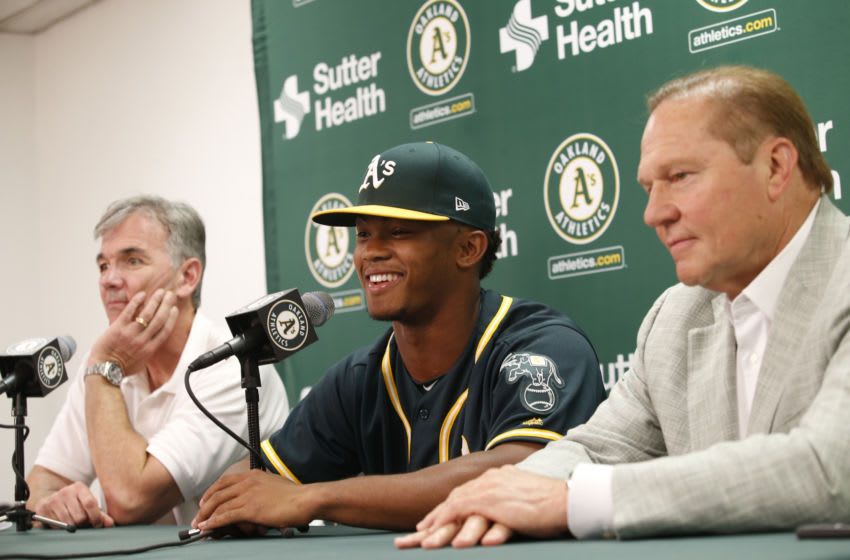 OAKLAND, CA - JUNE 15: Executive Vice President of Baseball Operations Billy Beane of the Oakland Athletics, first round draft pick Kyler Murray and Agent Scott Boras talk during a press conference after Murray signed his contact at the Oakland Alameda Coliseum on June 15, 2018 in Oakland, California. (Photo by Michael Zagaris/Oakland Athletics/Getty Images)