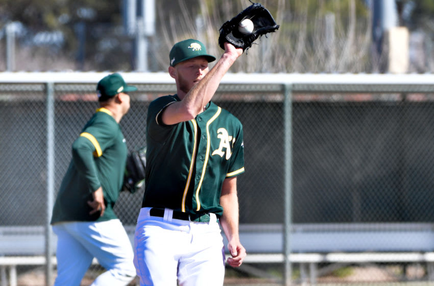 Feb 26, 2021; Mesa, Arizona, USA; Oakland Athletics pitcher A.J. Puk (33) catches a ball at first base during a spring training workout at the Lew Wolff Training Complex. Mandatory Credit: Matt Kartozian-USA TODAY Sports