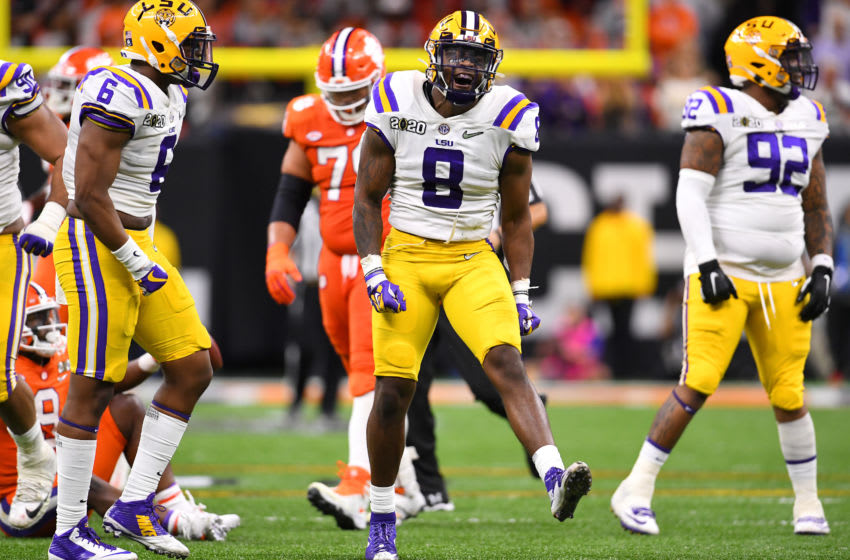 NEW ORLEANS, LA - JANUARY 13: Patrick Queen #8 of the LSU Tigers celebrates a tackle against Travis Etienne #9 of the Clemson Tigers during the College Football Playoff National Championship held at the Mercedes-Benz Superdome on January 13, 2020 in New Orleans, Louisiana. (Photo by Jamie Schwaberow/Getty Images)