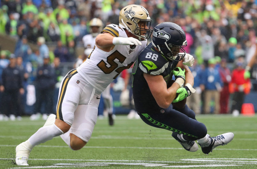 SEATTLE, WASHINGTON - SEPTEMBER 22: Will Dissly #88 of the Seattle Seahawks completes a pass against Kiko Alonso #54 of the New Orleans Saints in the third quarter during their game at CenturyLink Field on September 22, 2019 in Seattle, Washington. (Photo by Abbie Parr/Getty Images)