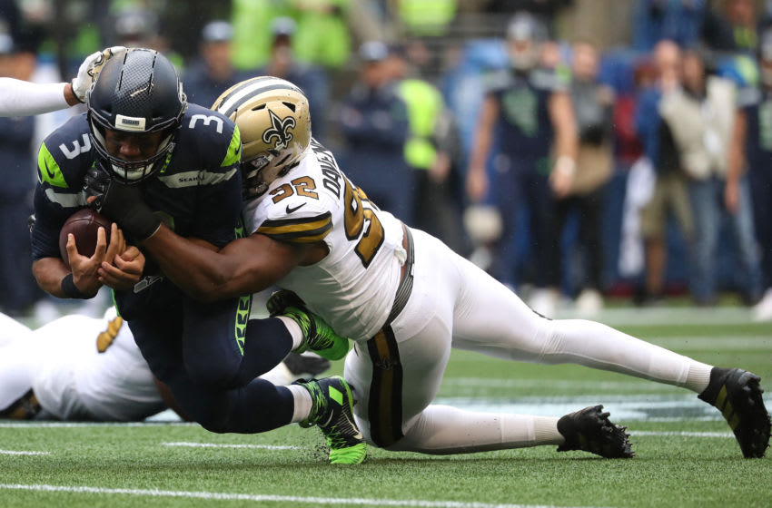 SEATTLE, WASHINGTON - SEPTEMBER 22: Russell Wilson #3 of the Seattle Seahawks is tackled by Marcus Davenport #92 of the New Orleans Saints in the first quarter during their game at CenturyLink Field on September 22, 2019 in Seattle, Washington. (Photo by Abbie Parr/Getty Images)