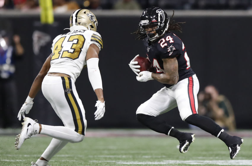 ATLANTA, GA - NOVEMBER 28: Devonta Freeman #24 of the Atlanta Falcons rushes as Marcus Williams #43 of the New Orleans Saints defends during the second half of an NFL game at Mercedes-Benz Stadium on November 28, 2019 in Atlanta, Georgia. (Photo by Todd Kirkland/Getty Images)