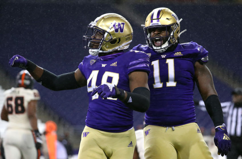 SEATTLE, WASHINGTON - NOVEMBER 14: Edefuan Ulofoshio #48 of the Washington Huskies celebrates with Josiah Bronson #11 after making a tackle in the first quarter against the Oregon State Beavers at Husky Stadium on November 14, 2020 in Seattle, Washington. (Photo by Abbie Parr/Getty Images)
