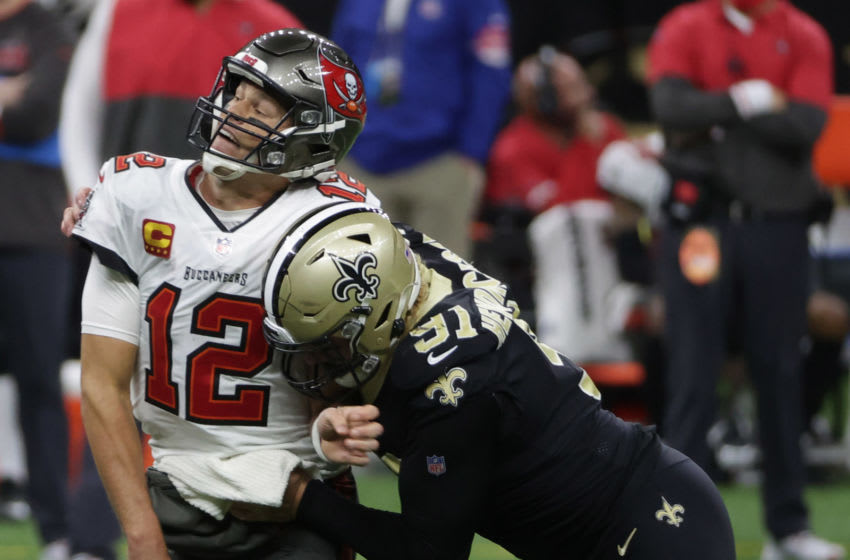Jan 17, 2021; New Orleans, LA, USA; Tampa Bay Buccaneers quarterback Tom Brady (12) is hit by New Orleans Saints defensive end Trey Hendrickson (91) during a NFC Divisional Round playoff game at Mercedes-Benz Superdome. Mandatory Credit: Derick E. Hingle-USA TODAY Sports