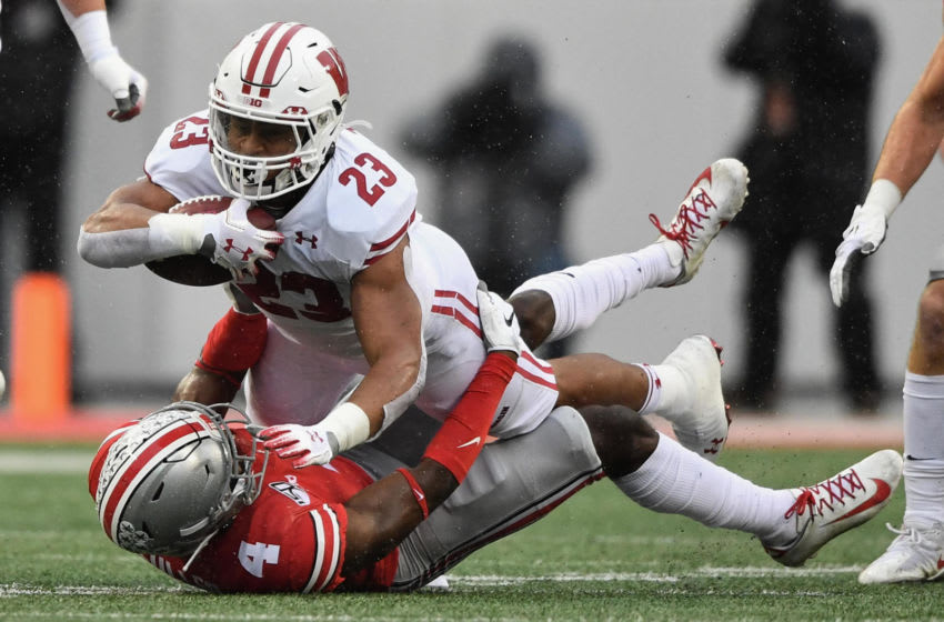 COLUMBUS, OH - OCTOBER 26: Jonathan Taylor #23 of the Wisconsin Badgers is brought down by Jordan Fuller #4 of the Ohio State Buckeyes after picking up a first down in the first quarter at Ohio Stadium on October 26, 2019 in Columbus, Ohio. (Photo by Jamie Sabau/Getty Images)