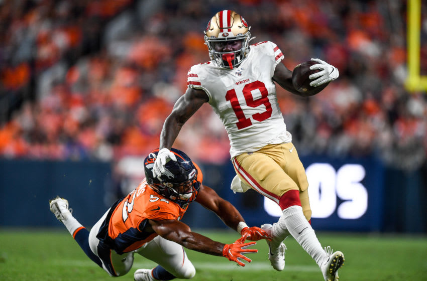 DENVER, CO - AUGUST 19: Wide receiver Deebo Samuel #19 of the San Francisco 49ers avoids a tackle attempt by linebacker Justin Hollins #52 of the Denver Broncos before a 45 yard gain against the Denver Broncos in the third quarter during a preseason National Football League game at Broncos Stadium at Mile High on August 19, 2019 in Denver, Colorado. (Photo by Dustin Bradford/Getty Images)