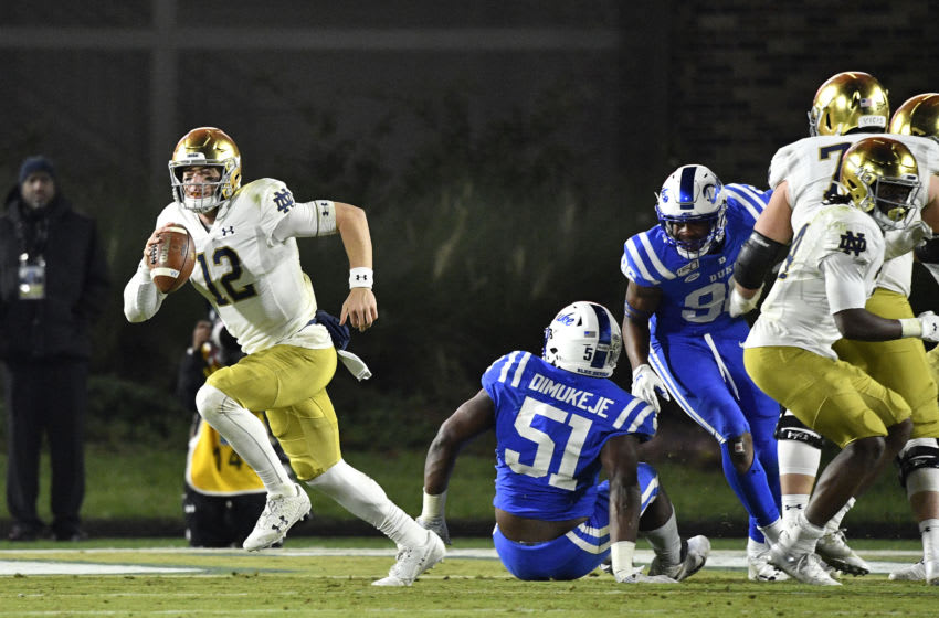 DURHAM, NORTH CAROLINA - NOVEMBER 09: Ian Book #12 of the Notre Dame Fighting Irish sprints away from the Duke Blue Devils defense during the second half of their game at Wallace Wade Stadium on November 09, 2019 in Durham, North Carolina. (Photo by Grant Halverson/Getty Images)