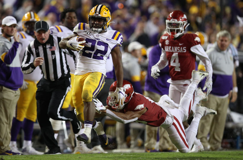 BATON ROUGE, LOUISIANA - NOVEMBER 23: Clyde Edwards-Helaire #22 of the LSU Tigers avoids a tackle by Jarques McClellion #4 of the Arkansas Razorbacks to score a touchdown at Tiger Stadium on November 23, 2019 in Baton Rouge, Louisiana. (Photo by Chris Graythen/Getty Images)