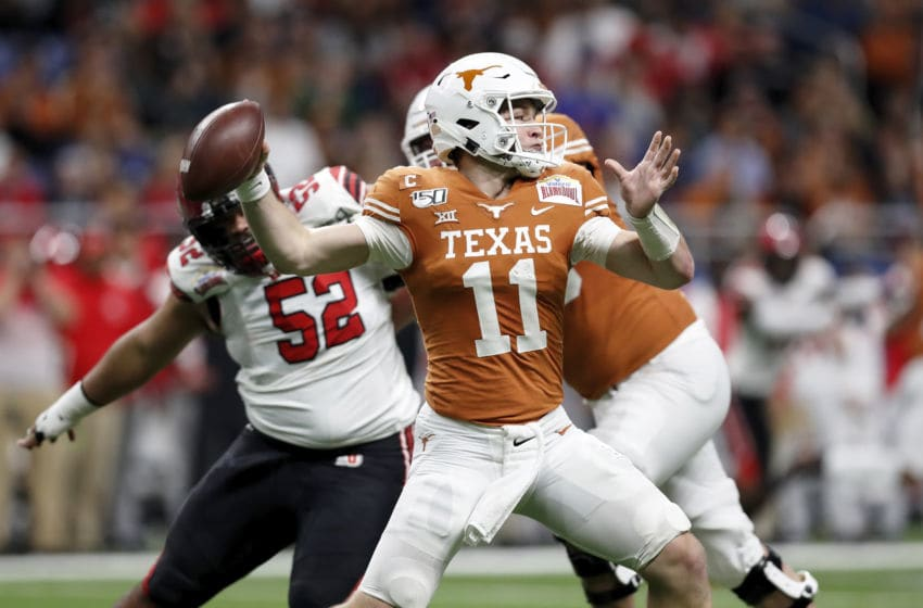 SAN ANTONIO, TX - DECEMBER 31: Sam Ehlinger #11 of the Texas Longhorns throws a pass under pressure by John Penisini #52 of the Utah Utes in the first quarter during the Valero Alamo Bowl at the Alamodome on December 31, 2019 in San Antonio, Texas. (Photo by Tim Warner/Getty Images)
