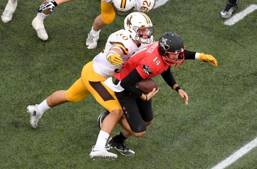 LAS VEGAS, NV - NOVEMBER 12: Linebacker Logan Wilson #30 of the Wyoming Cowboys tackles quarterback Kurt Palandech #14 of the UNLV Rebels after he rushed for five yards during their game at Sam Boyd Stadium on November 12, 2016 in Las Vegas, Nevada. UNLV won 69-66 in triple overtime. (Photo by Ethan Miller/Getty Images)