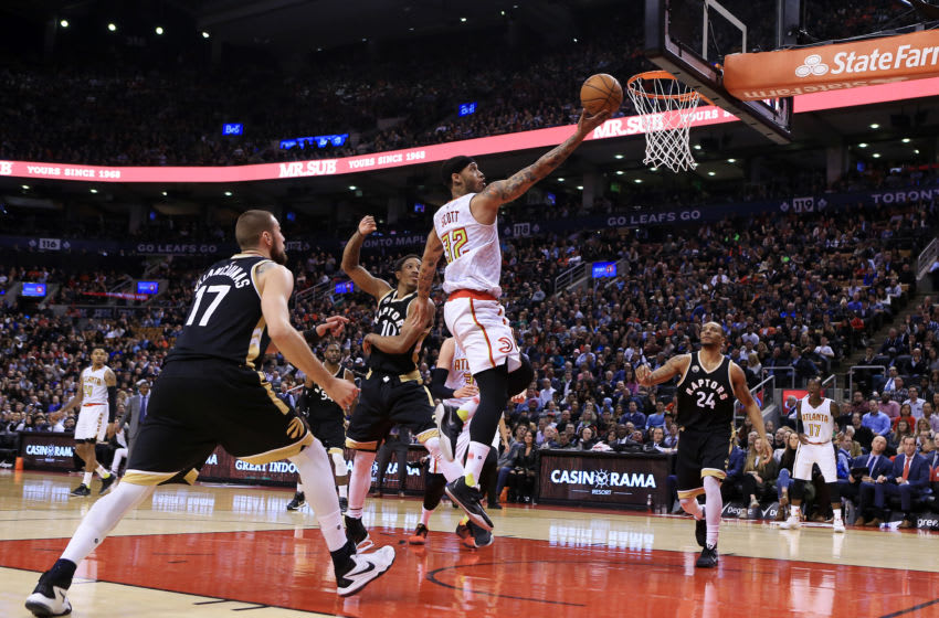 TORONTO, ON - MARCH 30: Mike Scott #32 of the Atlanta Hawks drives to the basket as Jonas Valanciunas #17 and DeMar DeRozan #10 of the Toronto Raptors defend during the second half of an NBA game at the Air Canada Centre on March 30, 2016 in Toronto, Ontario, Canada. (Photo by Vaughn Ridley/Getty Images)