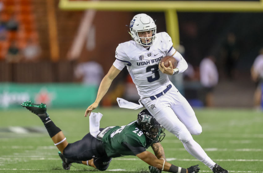 HONOLULU, HI - NOVEMBER 03: Henry Colombi #3 of the Utah State Aggies avoids a diving tackle attempt by Donovan Dalton #29 of the Hawaii Rainbow Warriors during the third quarter at Aloha Stadium on November 3, 2018 in Honolulu, Hawaii. (Photo by Darryl Oumi/Getty Images)