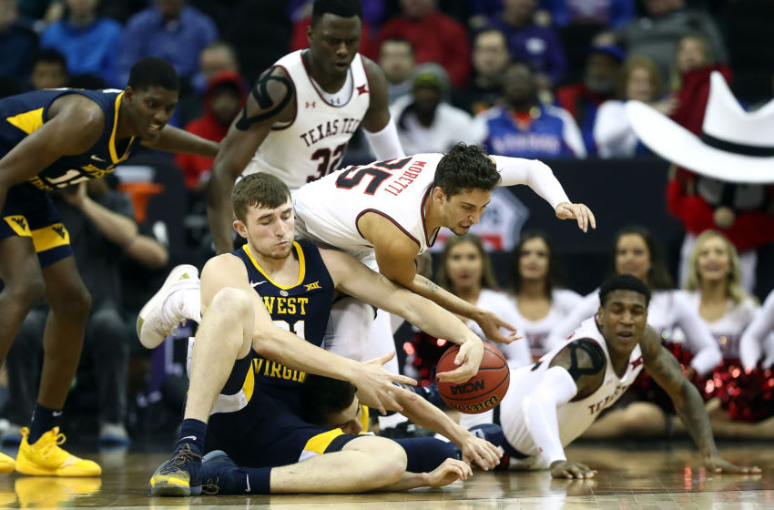 KANSAS CITY, MISSOURI - MARCH 14: Davide Moretti #25 of the Texas Tech Red Raiders and Logan Routt #31 of the West Virginia Mountaineers battle for a loose ball during the quarterfinal game of the Big 12 Basketball Tournament at Sprint Center on March 14, 2019 in Kansas City, Missouri. (Photo by Jamie Squire/Getty Images)