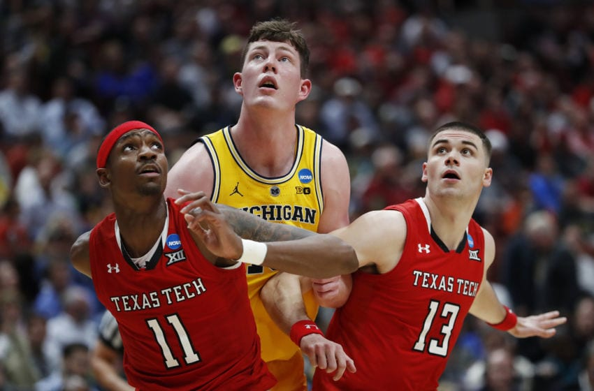 ANAHEIM, CALIFORNIA - MARCH 28: Jon Teske #15 of the Michigan Wolverines fights for position against Tariq Owens #11 and Matt Mooney #13 of the Texas Tech Red Raiders during the 2019 NCAA Men's Basketball Tournament West Regional at Honda Center on March 28, 2019 in Anaheim, California. (Photo by Sean M. Haffey/Getty Images)